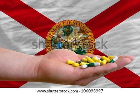 man holding capsules in front of complete wavy american state flag of florida symbolizing health, medicine, cure, vitamines and healthy life