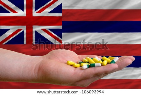 man holding capsules in front of complete wavy american state flag of hawaii symbolizing health, medicine, cure, vitamines and healthy life