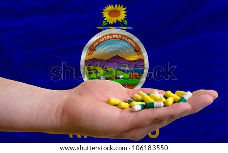 man holding capsules in front of complete wavy american state flag of kansas symbolizing health, medicine, cure, vitamins and healthy life