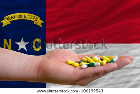 man holding capsules in front of complete wavy american state flag of north carolina symbolizing health, medicine, cure, vitamins and healthy life - stock photo