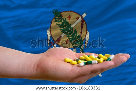 man holding capsules in front of complete wavy american state flag of oklahoma symbolizing health, medicine, cure, vitamins and healthy life