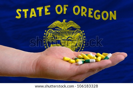 man holding capsules in front of complete wavy american state flag of oregon symbolizing health, medicine, cure, vitamins and healthy life