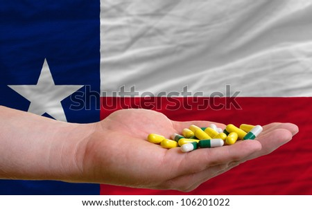 man holding capsules in front of complete wavy american state flag of texas symbolizing health, medicine, cure, vitamins and healthy life