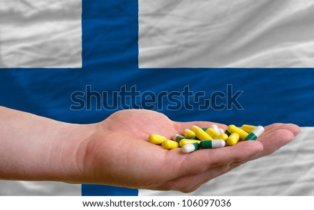 man holding capsules in front of complete wavy finland national flag of  symbolizing health, medicine, cure, vitamines and healthy life