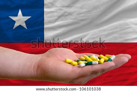 man holding capsules in front of complete wavy national flag of chile symbolizing health, medicine, cure, vitamins and healthy life