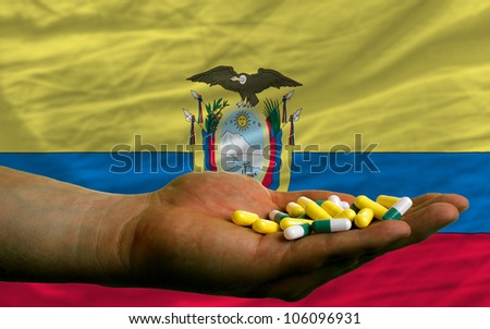 man holding capsules in front of complete wavy national flag of ecuador symbolizing health, medicine, cure, vitamines and healthy life