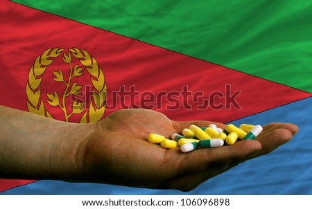man holding capsules in front of complete wavy national flag of eritrea symbolizing health, medicine, cure, vitamines and healthy life
