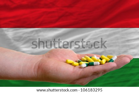 man holding capsules in front of complete wavy national flag of hungary symbolizing health, medicine, cure, vitamins and healthy life