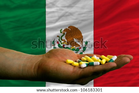 man holding capsules in front of complete wavy national flag of mexico symbolizing health, medicine, cure, vitamins and healthy life