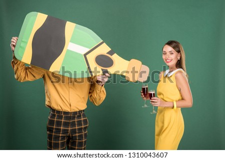 man holding cardboard bottle while beautiful woman in vintage clothes holding red wine glasses isolated on green
