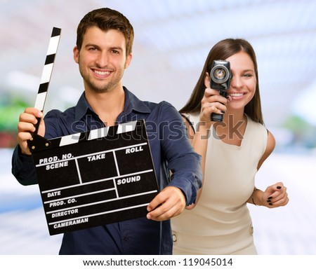 Man Holding Clapper Board And Woman Capturing Photo, Outdoors