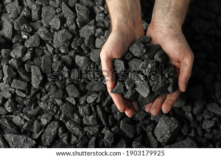 Man holding coal in hands over pile, top view. Space for text Imagine de stoc ©