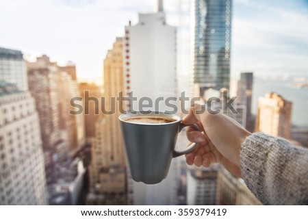 Stock Photo Man holding coffee cup in luxury penthouse apartments with view to New York City Manhattan downtown at the morning
