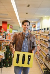 Man holding crate of beer in an organic grocery store