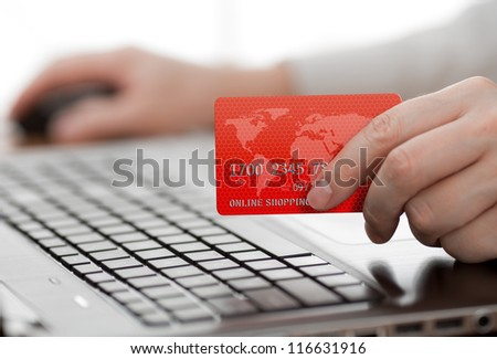 Man holding credit card in hand and entering security code using laptop keyboard