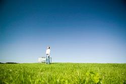 Man holding deckchair in field