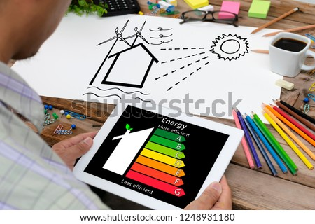 Man holding digital tablet and looking at house efficiency rating. Detail of house efficiency rating on digital tablet screen. Concept of ecological and bio energetic house. Energy class.