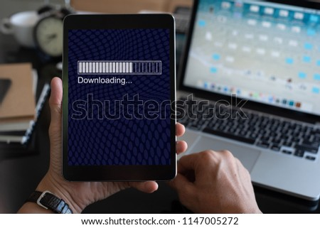 Man holding digital tablet with mobile apps downloading on futuristic technology screen with laptop computer as background, close up #1147005272