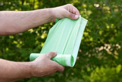 Man holding eco plastic garbage bio bag in roll outdoors, bag for composting organic trash