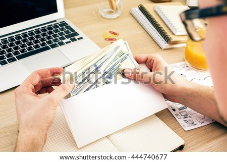 Man holding envelope with money above wooden office desktop with various items. Bribery and corruption concept #444740677