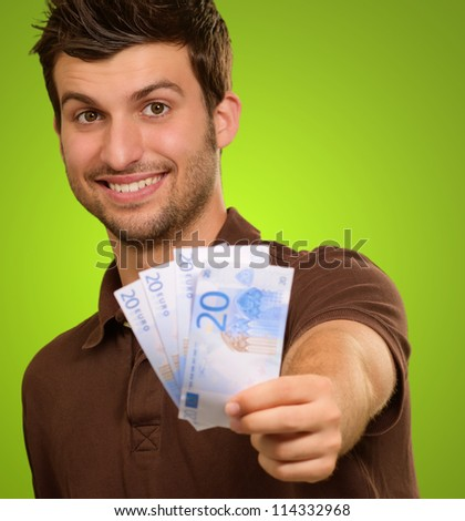 Man Holding Euro Currency On Green Background