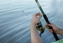 man holding fish bait and fishing rod in his hands.Hobby and leisure concept.