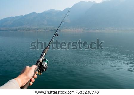 man holding fishing rod, fishing pole over the lake. #583230778
