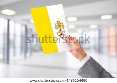 Man Holding Flag of Holy See. Holy See in Hand.