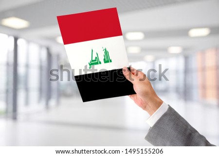 Man Holding Flag of Iraq. Iraq in Hand.