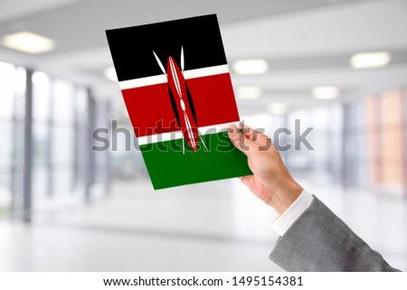 Man Holding Flag of Kenya. Kenya in Hand.