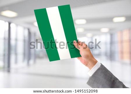 Man Holding Flag of Nigeria. Nigeria in Hand. #1495152098