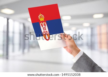 Man Holding Flag of Serbia. Serbia in Hand. #1495152038