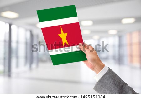 Man Holding Flag of Suriname. Suriname in Hand. #1495151984