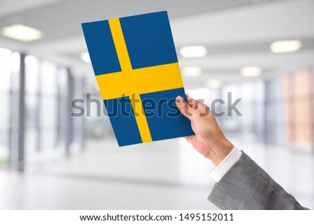 Man Holding Flag of Sweden. Sweden in Hand.