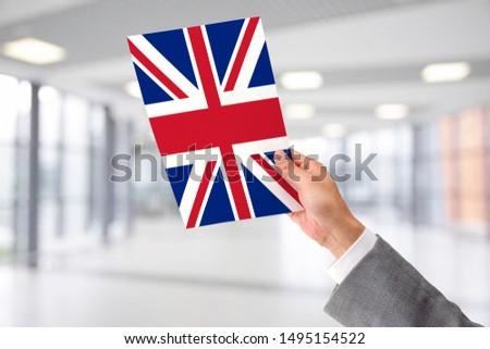 Man Holding Flag of United Kingdom. United Kingdom in Hand.