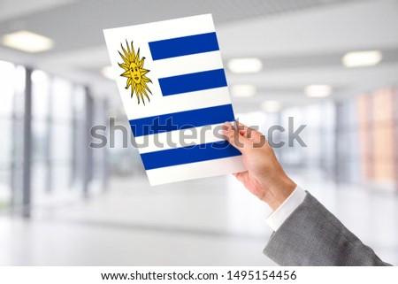 Man Holding Flag of Uruguay. Uruguay in Hand. #1495154456