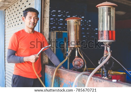 man holding fuel nozzle at...