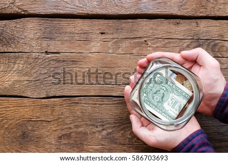 man holding glass jar of fundraising #586703693
