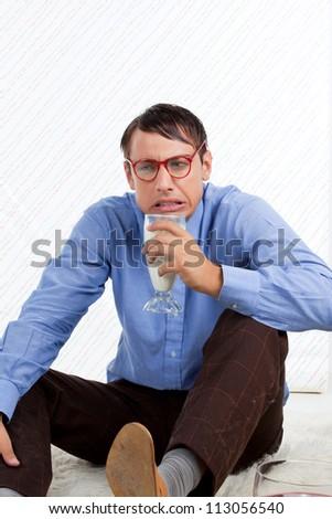 Man holding glass of milk sitting on rug.