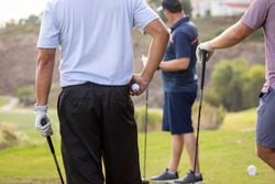 Man holding golf ball with friends at a gold course