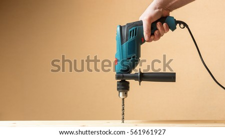 Man holding green drill and drilling lining woods. Yellow orange copy space wall