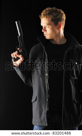 Man holding gun with silencer over black
