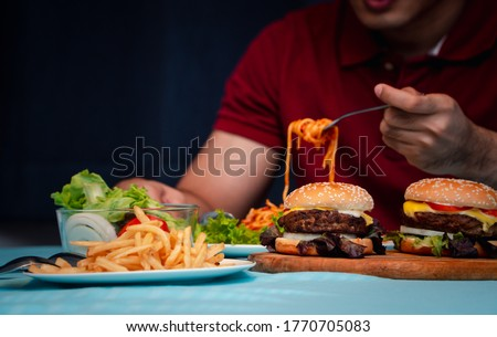 Man holding hamburger on the wooden plate after delivery man delivers foods at home. Concept of binge eating disorder (BED) and Relaxing with Eating junk food. Stock photo ©
