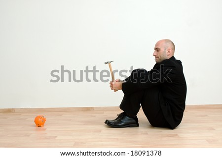 Man holding hammer looking at an orange piggy bank.
