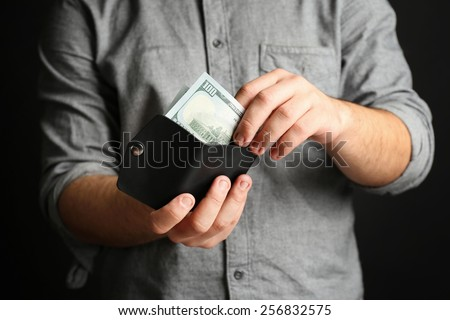 Man holding hand made leather wallet with money on black background