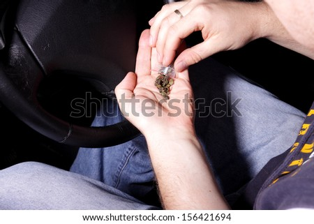 man holding hashish in the car