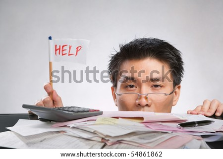 Man holding help flag made of paper and pencil with lots of bills in front of him