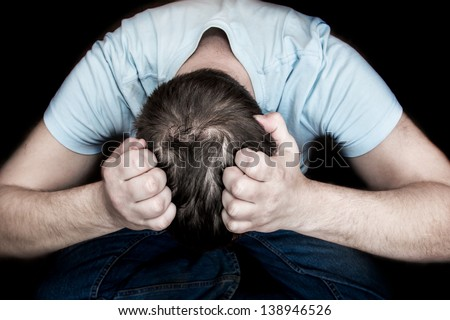 Man holding his head in his hands sitting on floor over black background. Despair, depression, hopelessness concept.