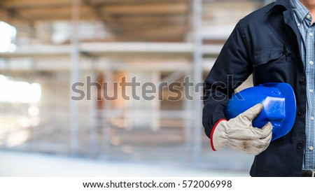 Man holding his helmet in a construction site