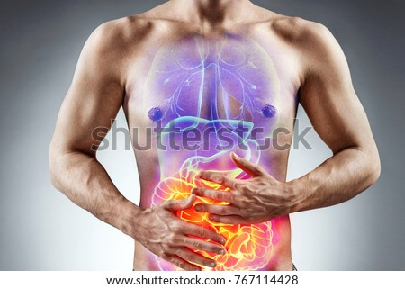 Man holding his stomach in pain. Photo of man with naked torso experience irritable bowel syndrome on grey background. Medical concept